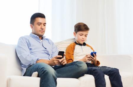 problemas familiares: el ocio, la tecnología, la tecnología, la familia y las personas concepto - padre e hijo con smartphones mensajes de texto mensaje o jugando partido en casa