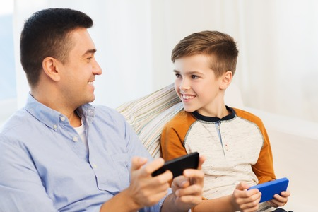 leisure, technology, technology, family and people concept - happy father and son with smartphones talking at home