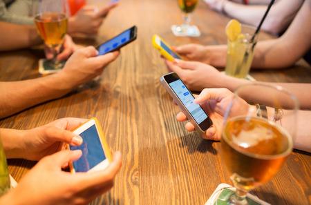 vrije tijd, technologie, lifestyle en mensen concept - close-up van de handen met smartphones messaging bij restaurant Stockfoto