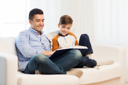 fatherhood: family, fatherhood, generation, literature and people concept - happy father and son reading book at home Stock Photo
