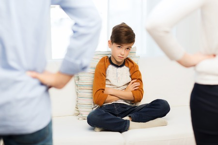people, misbehavior, family and relations concept - close up of upset or feeling guilty boy and parents at home Foto de archivo