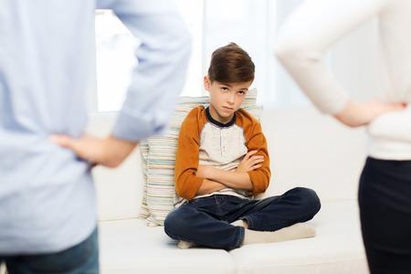 Menschen, Fehlverhalten, Familien- und Beziehungskonzept - Nahaufnahme von verärgertem oder schuldigem Jungen und Eltern zu Hause