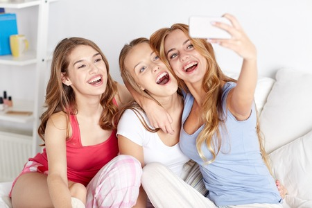 teenage girl happy: friendship, people, pajama party and technology concept - happy friends or teenage girls with smartphone taking selfie at home