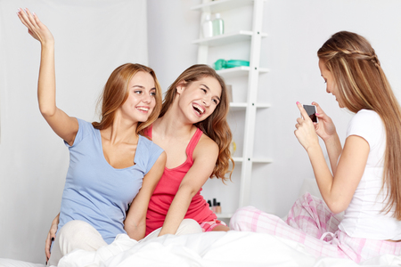 in pajama: friendship, people, pajama party and technology concept - happy friends or teenage girls with smartphone taking picture at home Stock Photo