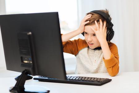 vrije tijd, onderwijs, kinderen, technologie en mensen concept - doodsbange jongen met een computer en een koptelefoon afspelen van video game thuis