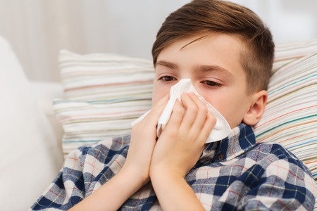 childhood, healthcare, rhinitis, people and medicine concept - ill boy with flu lying in bed and blowing his nose at home Archivio Fotografico
