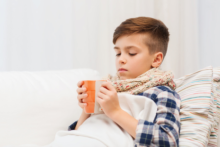 pre teen boys: childhood, healthcare, people and medicine concept - ill boy with flu lying in bed and drinking tea at home