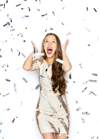 people, holidays, emotion and glamour concept - happy young woman or teen girl in fancy dress with sequins and confetti at party Standard-Bild