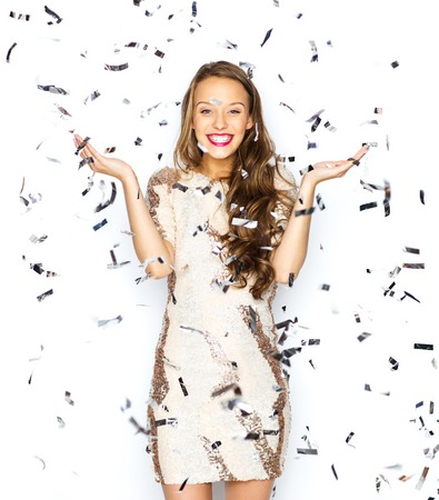 people, holidays, emotion and glamour concept - happy young woman or teen girl in fancy dress with sequins and confetti at party Banco de Imagens