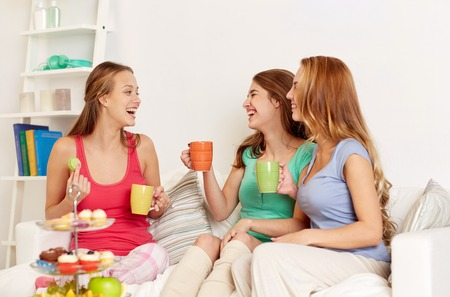 pajama party: friendship, people, pajama party and communication concept - happy friends or teenage girls drinking tea and eating sweets at home