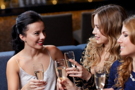 お祝い、お友達、独身パーティーや休日のコンセプト - 夜のクラブでシャンパン グラスを持つ幸せな女性