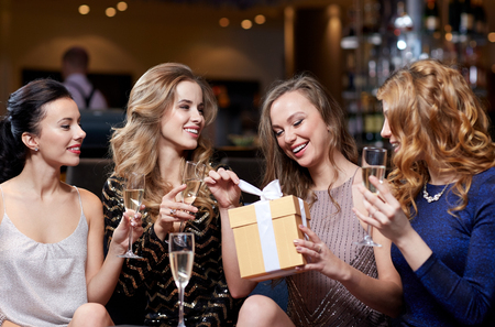 wine gift: celebration, friends, bachelorette party, birthday and holidays concept - happy women with champagne glasses and gift box at night club