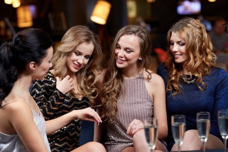 showing: celebration, friends, bachelorette party and holidays concept - happy woman showing engagement ring to her friends with champagne glasses at night club Stock Photo