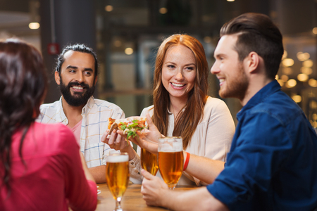 holiday gathering: leisure, food and drinks, people and holidays concept - smiling friends eating pizza and drinking beer at restaurant or pub Stock Photo