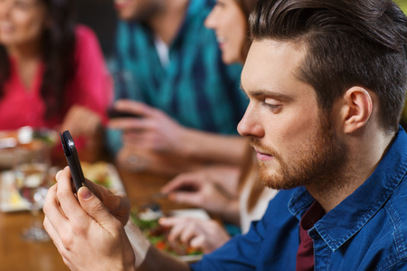 eating dinner: leisure, technology, internet addiction, lifestyle and people concept - man with smartphone and friends at restaurant Stock Photo