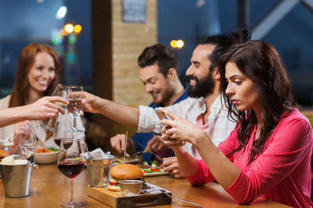 cell phone addiction: leisure, technology, internet addiction, lifestyle and people concept - woman with smartphone and friends at restaurant