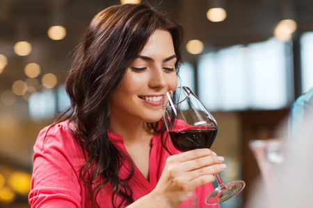 tasting: leisure, drinks, degustation, people and holidays concept - smiling woman drinking red wine at restaurant