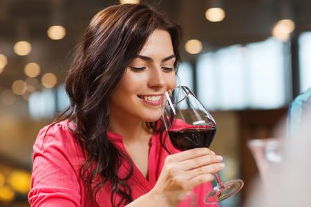 bebiendo vino: ocio, bebidas, degustación, la gente y el concepto de vacaciones - Mujer sonriente que bebe vino tinto en el restaurante Foto de archivo