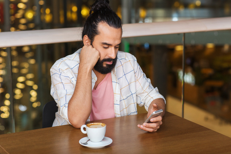 sad man alone: leisure, technology, lifestyle and people concept - man with smartphone and coffee at restaurant