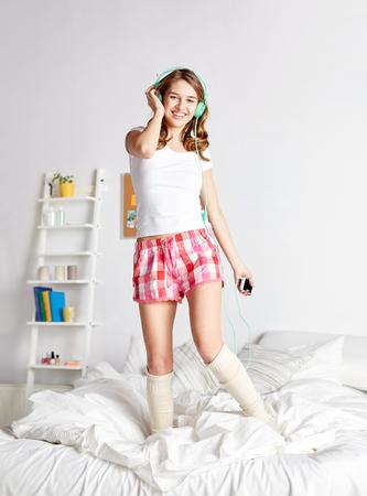 gente bailando: la gente, ocio y tecnolog�a concepto - mujer feliz o adolescente en los auriculares escuchando m�sica desde el tel�fono inteligente y bailando en la cama en su casa