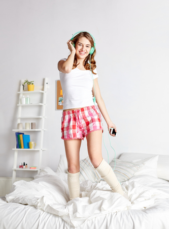 pj's: people, leisure and technology concept - happy woman or teenage girl in headphones listening to music from smartphone and dancing on bed at home