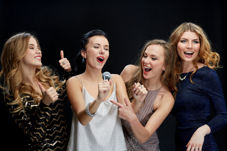 hen party: holidays, friends, bachelorette party, nightlife and people concept - three women in evening dresses with microphone singing karaoke over black background