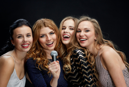 mics: holidays, friends, bachelorette party, nightlife and people concept - three women in evening dresses with microphone singing karaoke over black background