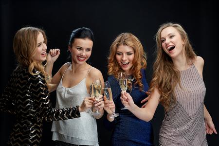 jovenes tomando alcohol: celebración, amigos, despedida de soltera y concepto de vacaciones - mujeres felices tintineo de copas de champán y bailando sobre fondo negro