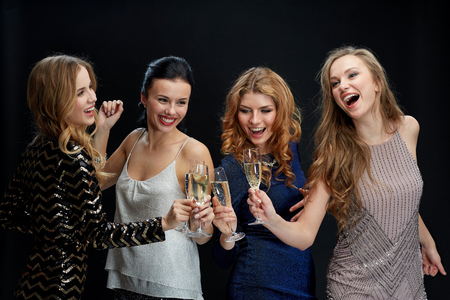 celebration, friends, bachelorette party and holidays concept - happy women clinking champagne glasses and dancing over black background