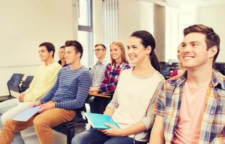 college: education, high school, teamwork and people concept - group of smiling students with notepads sitting in lecture hall Stock Photo