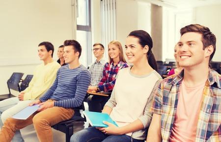edukacja, szkoła, praca zespołowa i ludzie koncepcja - grupa studentów uśmiechnięta z notesy siedzi w sali wykładowej