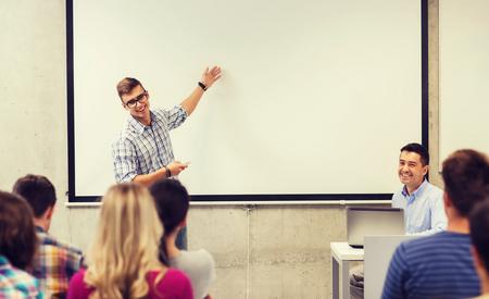 onderwijs, middelbare school, technologie en mensen concept - student die zich met afstandsbediening, laptop computer in de voorkant van de leraar en klasgenoten in de klas Stockfoto