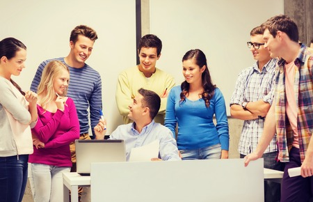 education, high school, technology and people concept - group of smiling students and teacher with papers, laptop computer in classroom