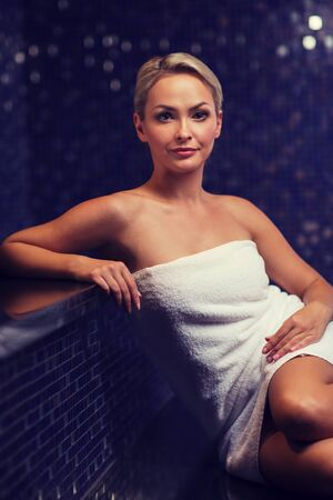 turkish woman: people, beauty, spa, healthy lifestyle and relaxation concept - beautiful young woman sitting in bath towel