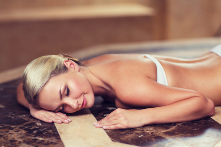 bath: people, beauty, spa, healthy lifestyle and relaxation concept - beautiful young woman lying on hammam table in turkish bath Stock Photo