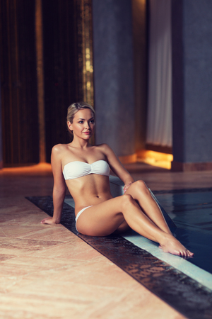 spa woman: people, beauty, spa, healthy lifestyle and relaxation concept - beautiful young woman in bikini swimsuit sitting on swimming pool edge Stock Photo