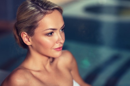 bodycare: people, beauty, spa, healthy lifestyle and relaxation concept - close up of beautiful young woman in swimsuit at swimming pool