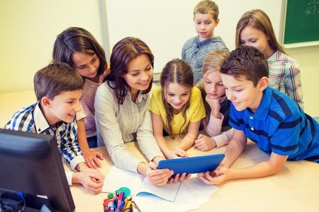 Educación, escuela primaria, el aprendizaje, la tecnología y el concepto de la gente - grupo de niños de la escuela con el maestro mira al ordenador Tablet PC en el aula Foto de archivo - 51849987