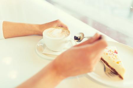 Freizeit, Essen und Trinken, Menschen und Lifestyle-Konzept - Nahaufnahme Kuchen der jungen Frau, die Hände zu essen und Kaffee im Café trinken