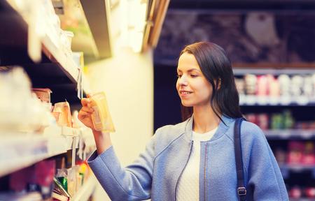 vente, achats, le consumérisme et les gens le concept - jeune femme heureuse choisir et acheter de la nourriture sur le marché
