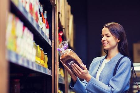 vente, achats, la consommation et les gens concept - jeune femme heureuse choisir et d'acheter du pain dans le marché Banque d'images