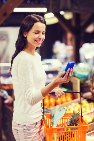 shopper: sale, shopping, consumerism and people concept - happy young woman with food basket and smartphone in market Stock Photo