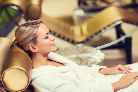bath robe: people, beauty, healthy lifestyle and relaxation concept - beautiful young woman lying on chaise-longue in bath robe at spa