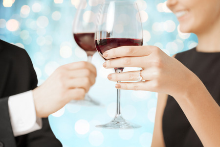 people, holidays, marriage and celebration concept - happy engaged couple clinking wine glasses over blue holidays lights background Stock Photo