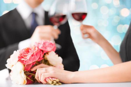matrimonio feliz: las personas, las vacaciones, el matrimonio y el concepto de la celebración - pareja comprometida feliz con copas de vino flor tintineo sobre fondo azul luces