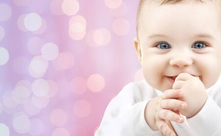 infancy: children, holidays, people, infancy and age concept - happy baby over pink lights background Stock Photo