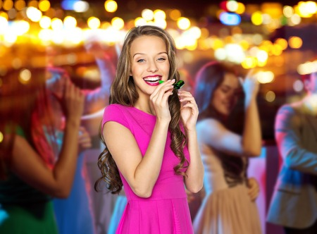 people, holidays and celebration concept - happy young woman or teen girl in pink dress blowing to party horn at night club over crowd and lights background
