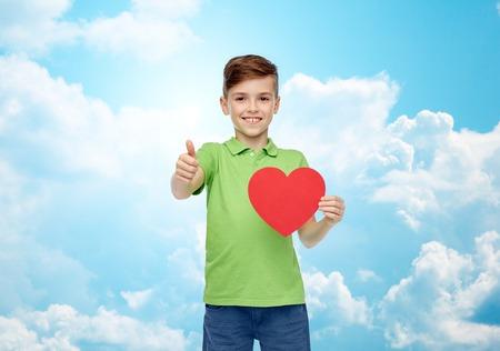 forme et sante: enfance, l'amour, la charité, les soins de santé et les gens concept - garçon souriant heureux t-shirt de polo vert tenant en blanc en forme de coeur rouge et montrant thumbs up sur le ciel bleu et nuages ??fond Banque d'images