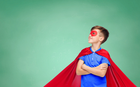 pre adolescent boy: school, education, childhood, power and people concept - happy boy in red super hero cape and mask over green chalk board background Stock Photo