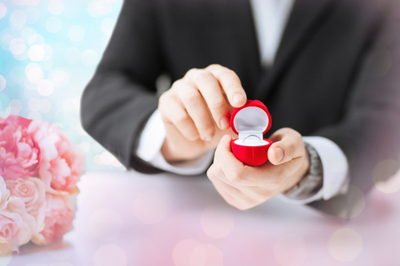 diamond ring: people, holidays, presents and proposal concept - close up of man with gift box and engagement ring over holidays lights background